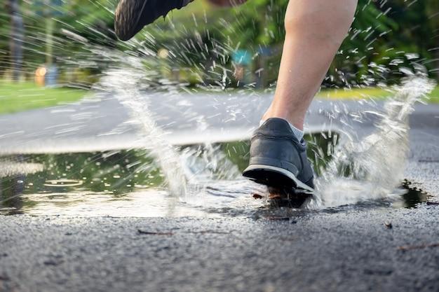 Exercício do homem que corre através da poça que espirra suas sapatas.