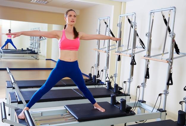 Exercício do split do lado da mulher do reformista de pilates
