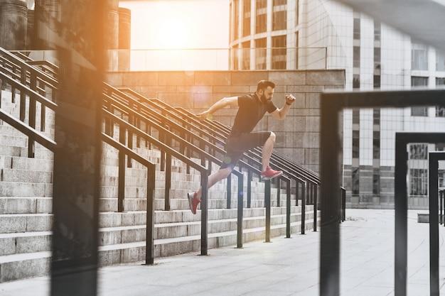 Exercício duro para atingir objetivos. jovem bonito em roupas esportivas pulando