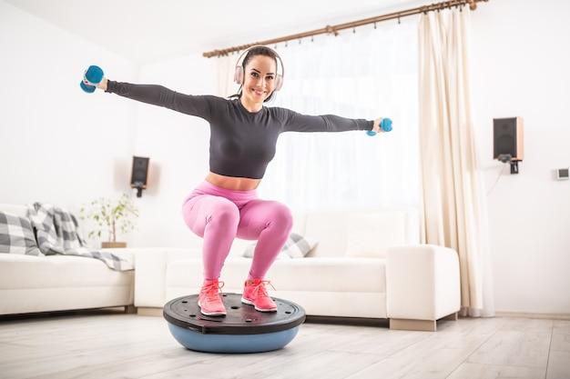 Exercício em casa por uma jovem em forma de casa agachada em uma bola de equilíbrio com os braços estendidos para o lado segurando halteres.