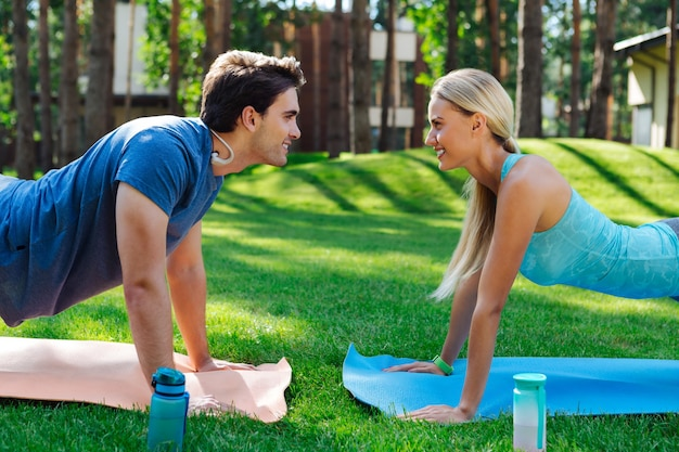 Exercício esportivo. pessoas positivas e alegres sorrindo umas para as outras enquanto fazem flexões
