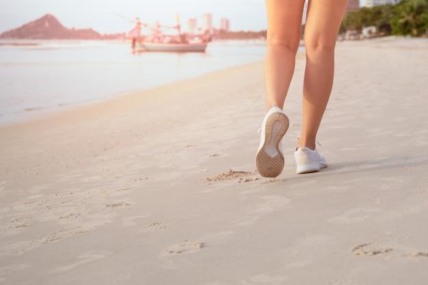 Exercício feminino andando na praia pela manhã.
