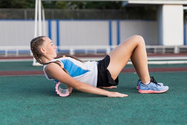 Exercício feminino jovem com rolo no estádio