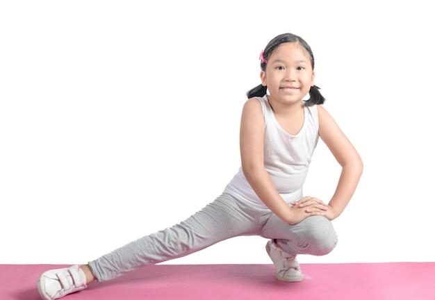 Exercício haealthy asiático da criança na esteira da ioga isolada no conceito branco do fundo, do lazer e do estilo de vida