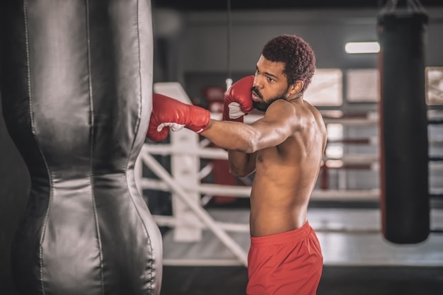 Exercício. kickboxer afro-americano se exercitando em uma academia trabalhando em seus chutes