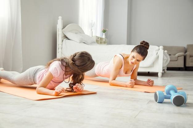 Exercício. linda e inspirada jovem mãe de cabelos escuros fazendo alguns exercícios com a filha enquanto está deitada no chão e olhando para sua filha