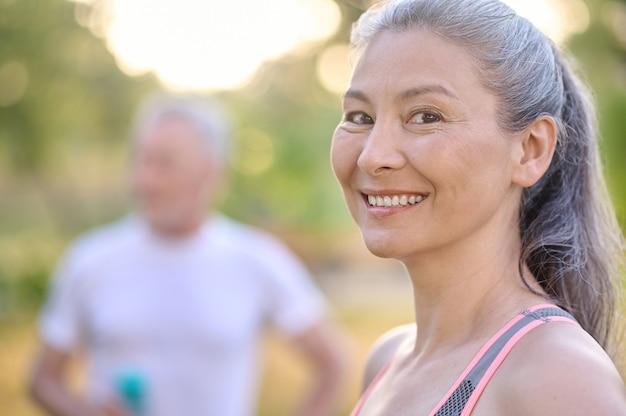 Exercício matinal. uma foto de uma mulher bem madura e um homem parado ao lado dela