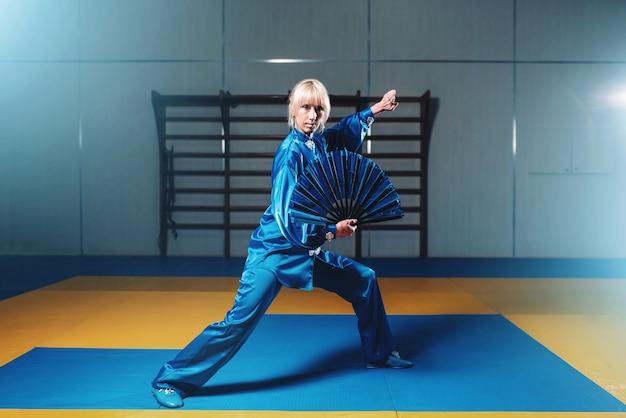 Exercício mestre de wushu feminino com ventilador, artes marciais. mulher vestida de azul em treino de luta