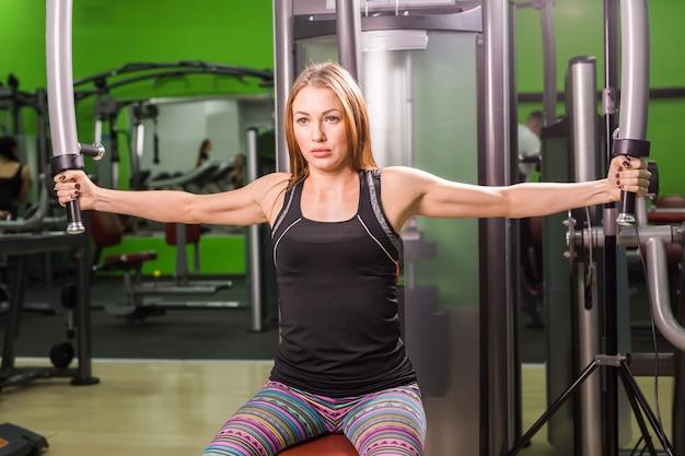 Exercício muscular bonito da mulher do ajuste