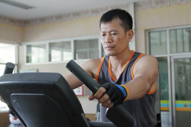 Exercício no ginásio, homem andando na esteira.