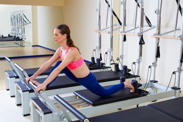 Exercício rachado da parte dianteira da mulher do reformista de pilates