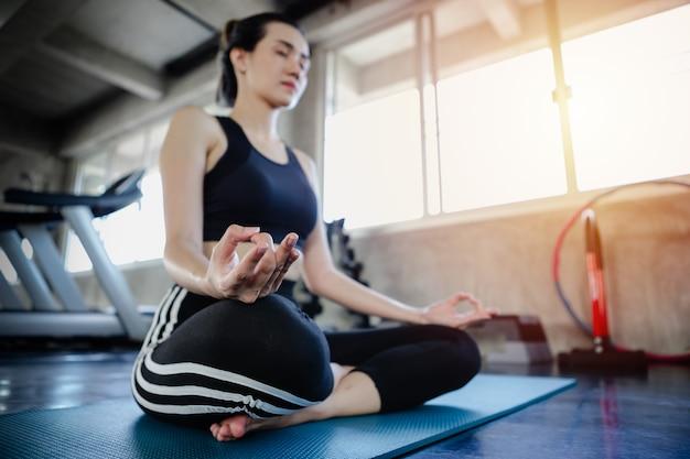 Exercício saudável do corpo do estilo de vida asiático da jovem mulher no gym, conceito da ioga do estilo dos esportes