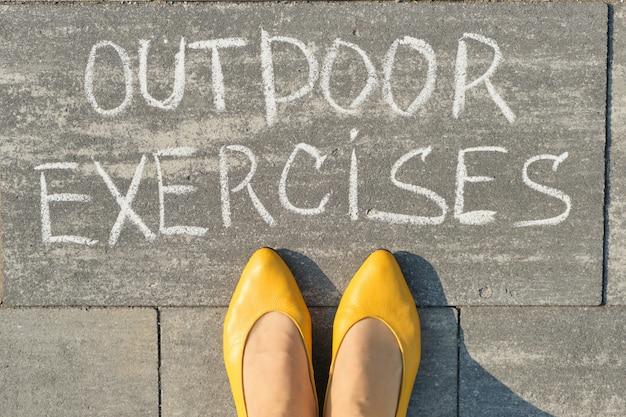 Exercícios ao ar livre, escritos na calçada cinza com pernas de mulher, vista superior