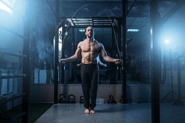 Exercícios de atleta muscular com pular corda no ginásio. esportista no treinamento físico.