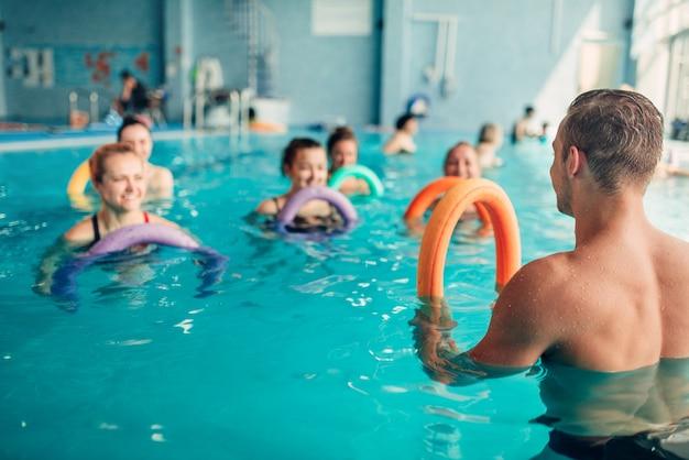 Exercícios de hidroginástica, aula feminina com treinador masculino, piscina coberta, lazer recreativo