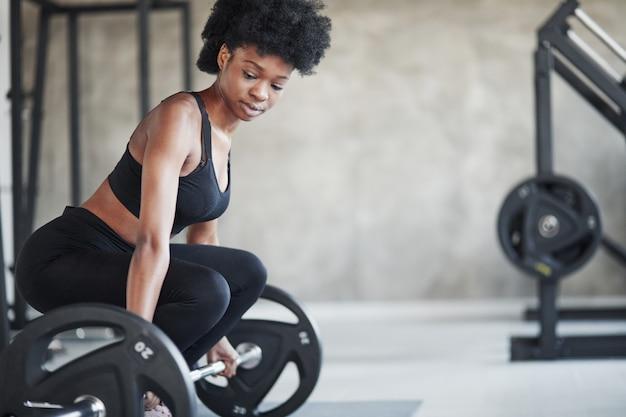 Exercícios de levantamento. mulher afro-americana com cabelo encaracolado e roupas esportivas tem um dia de ginástica na academia