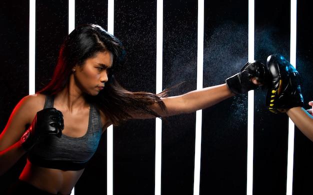 Exercícios de menina no ginásio moderno de boxe de néon pesadamente