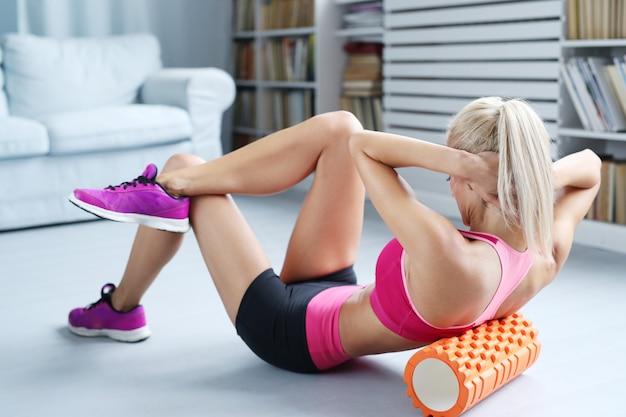 Exercícios de treino de mulher loira com rolo de espuma