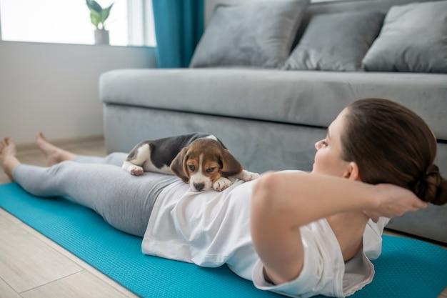 Exercícios matutinos. uma menina com uma camiseta branca se exercitando junto com seu cachorrinho