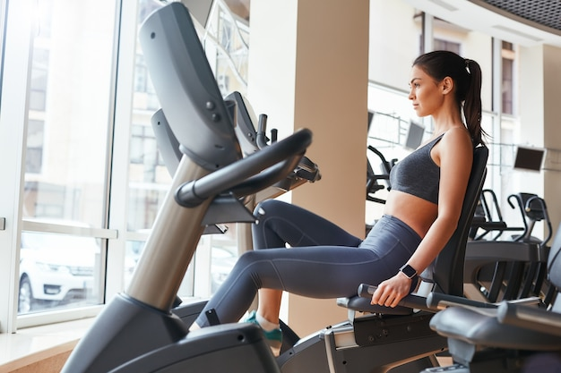 Exercitando a vista lateral de uma jovem mulher bonita com corpo perfeito em roupas esportivas e relógio inteligente
