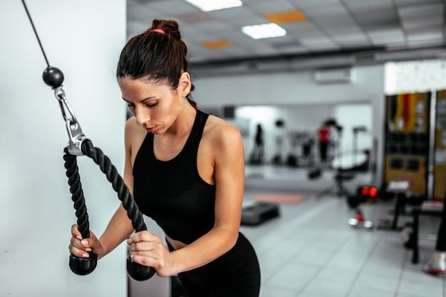 Exercitando com máquina de peso de cabo no ginásio.