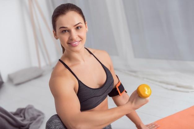 Exercitando meus braços. mulher jovem atlética de cabelos escuros muito alerta sorrindo e fazendo exercícios com pesos de mão enquanto está sentada no tapete em casa