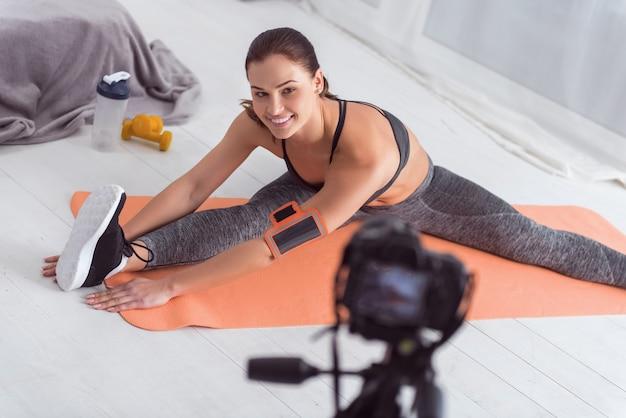 Exercitar muito. linda e inspirada jovem mulher de cabelos escuros sorrindo e se espreguiçando enquanto está sentada no tapete e fazendo um vídeo para seu blog