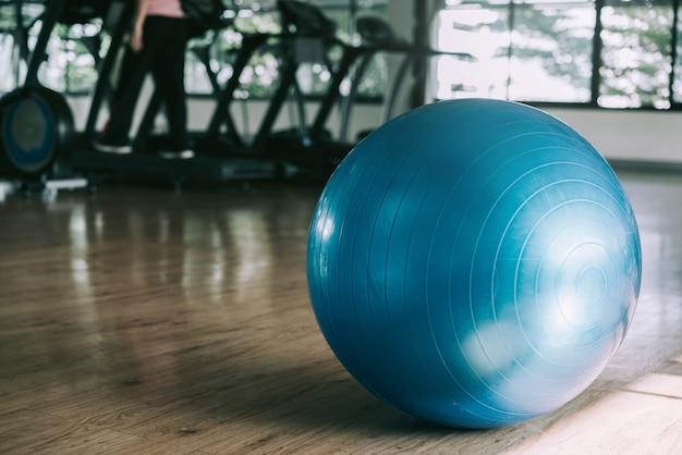 Exercite a bola azul da cor na aptidão, no equipamento do gym e nas bolas da aptidão no clube desportivo.