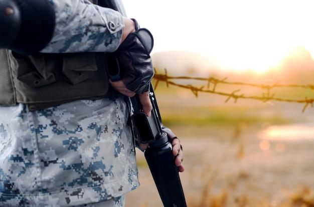 Exército de foco selecionado com arma rifle com cerca de arame de fundo desfocado