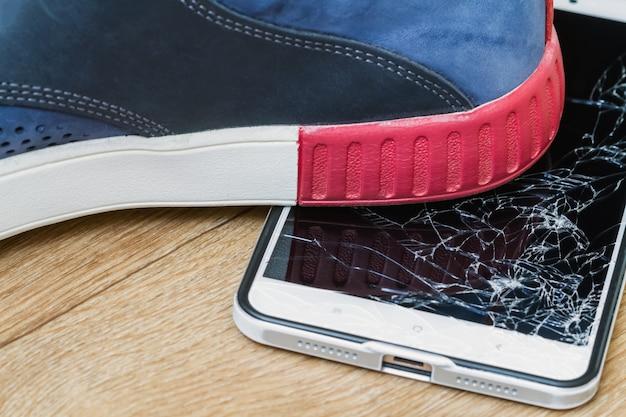Exibição de smartphone esmagada pelo boot no fundo marrom