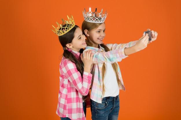 Exija mais atenção. crianças usam coroas douradas símbolo de princesa. sinais de alerta de criança mimada. evite criar filhos mimados. meninas tirando foto da câmera do smartphone selfie. conceito de crianças mimadas.
