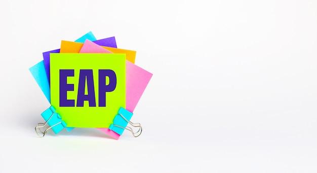 Existem adesivos coloridos brilhantes com o texto programa de assistência ao funcionário eap. copie o espaço