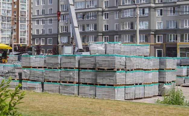 Existem muitas novas lajes de pavimentação cinza em paletes cobertas de plástico no canteiro de obras. pavimentação de vias pedonais numa rua da cidade. primeiro plano. reparo da calçada da praça da cidade.