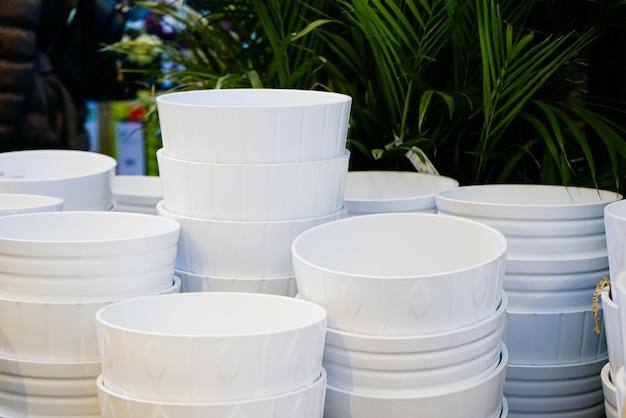 Existem muitos vasos brancos sob as flores e plantas