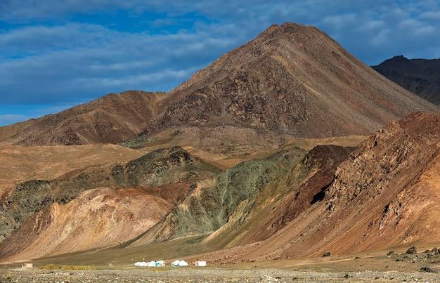 Existem pequenos yurts mongóis e casas arruinadas perto das montanhas altai, na mongólia ocidental, ásia