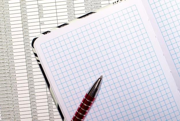 Existem relatórios na área de trabalho. eles têm um caderno aberto e em branco e uma caneta.