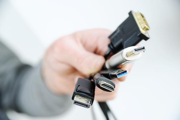 Existem vários cabos e plugues nas mãos de um homem.