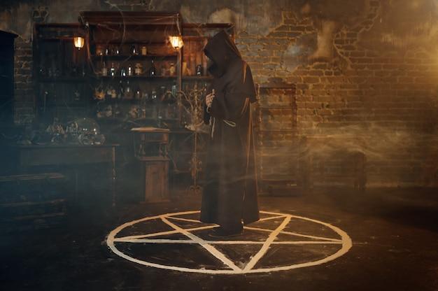 Exorcista masculino com capuz preto em pé no círculo mágico. exorcismo, ritual paranormal de mistério, religião das trevas, terror noturno, poções na prateleira