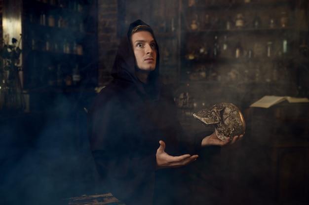 Exorcista masculino com capuz preto segura um crânio humano. exorcismo, ritual paranormal de mistério, religião das trevas, terror noturno, poções na prateleira