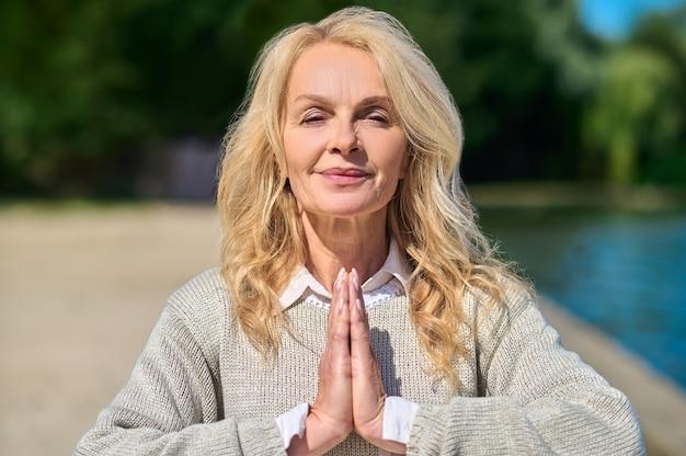 Expansão de consciência. linda mulher de meia-idade sorridente com um suéter claro em pose de namastê ao ar livre em um dia ensolarado