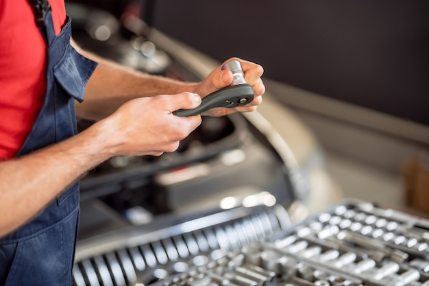 Experiência, habilidade. close de mãos masculinas trabalhando com uma peça na oficina de automóveis, o rosto do mecânico não é visível