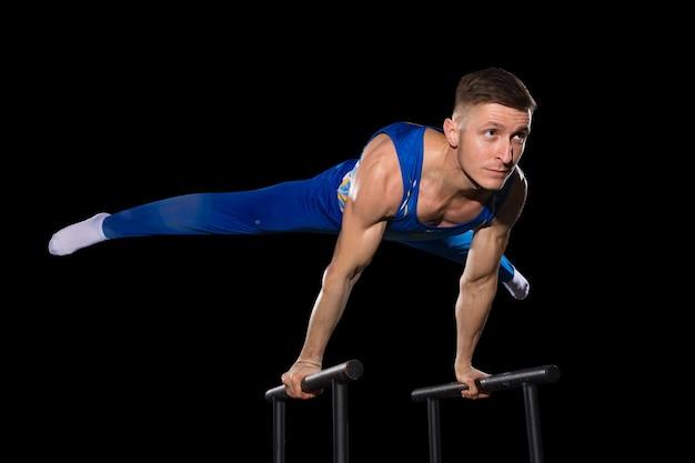 Experiência. treino de ginasta masculino musculoso em ginásio, flexível e ativo. cara apto caucasiano, atleta em sportswear azul, fazendo exercícios para força e equilíbrio. movimento, ação, movimento, conceito dinâmico.