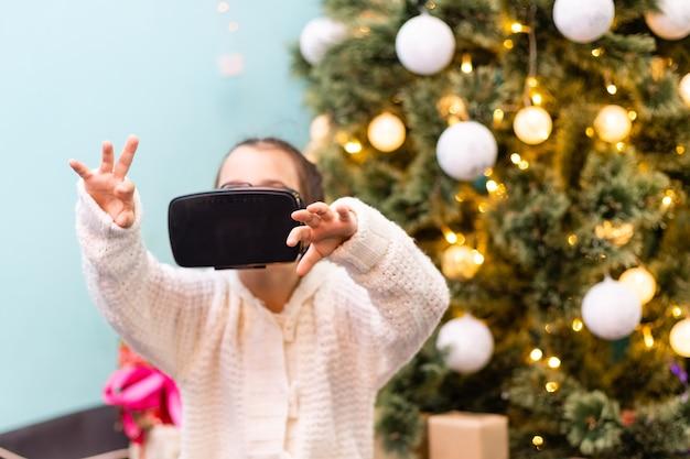 Experiência virtual. linda garota feliz e inteligente tocando os óculos de realidade virtual que ela usava ao sorrir perto da árvore de natal interna