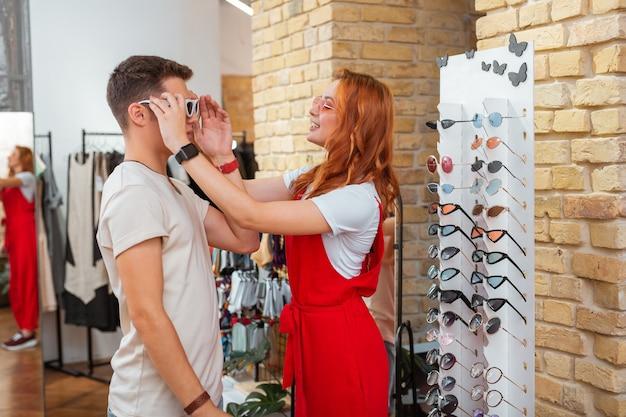 Experimentando óculos de sol. jovem gentil e cuidadosa colocando óculos escuros da moda no rosto de seu namorado calmo enquanto faz compras com ele