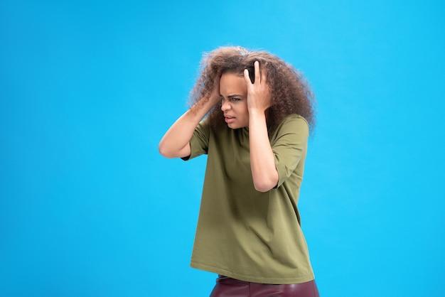 Experimentando uma jovem em pé, segurando a cabeça com as mãos em uma camiseta verde-oliva isolada na parede azul