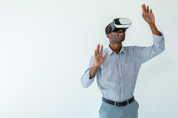Experimente em ação. homem afro-americano sorridente alegre usando óculos de realidade virtual em pé contra um fundo branco