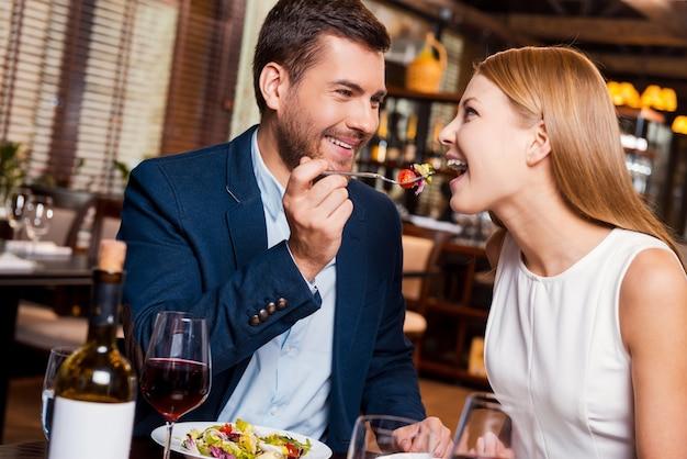 Experimente isso! jovem casal apaixonado apreciando o jantar no restaurante enquanto um homem alimenta a namorada com salada