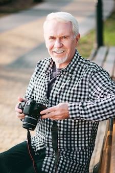 Experimente mais. homem maduro e alegre usando a câmera e descansando em um banco