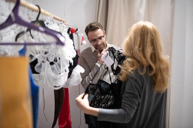 Experimente. marido e mulher alegres, escolhendo um conjunto de roupas íntimas para ela em uma loja de lingerie.