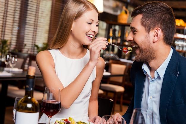 Experimente minha refeição! jovem casal apaixonado apreciando o jantar no restaurante enquanto uma mulher alimenta o namorado com salada